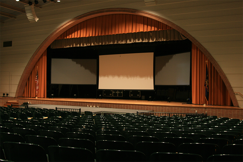 the inside of the Octorara Area High School auditorium featuring complex curved walls and an arch framing the stage