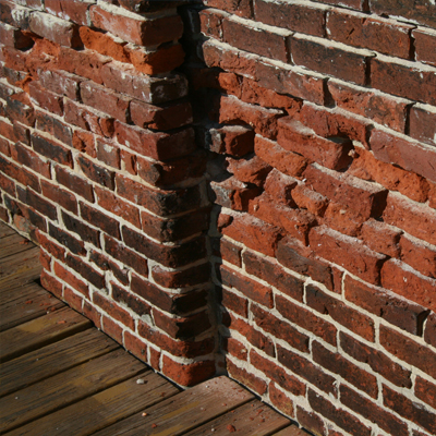 a wall suffering from deterioriated mortar joints due to lack of maintenance