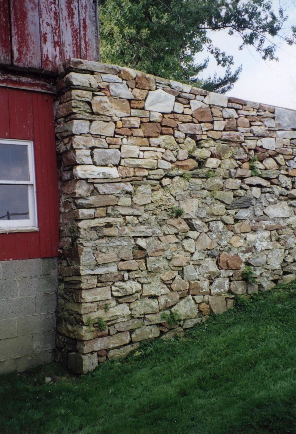 A Natural Stone Wall Attached To An Old Red Barn