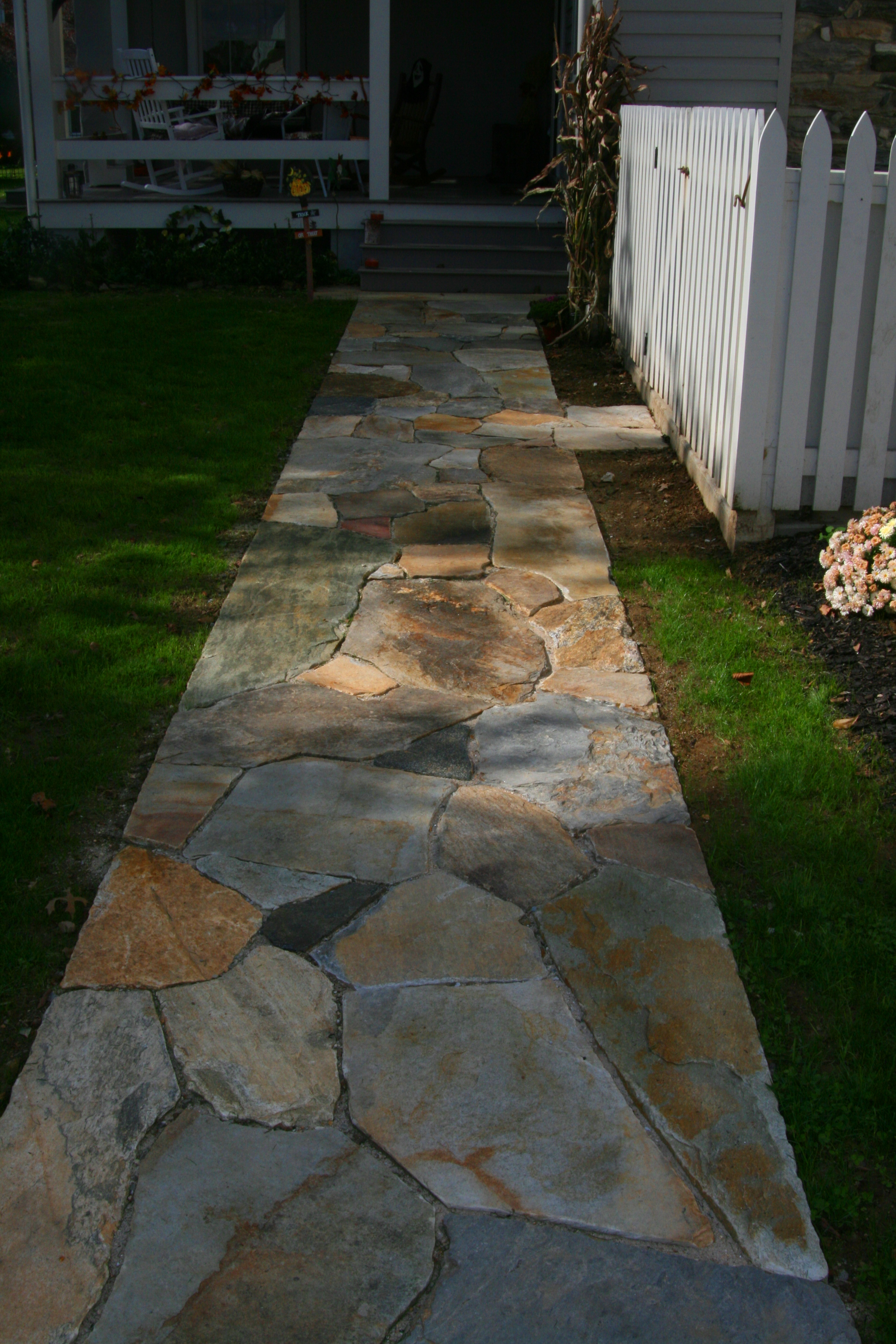 A Newly Installed Stone Sidewalk Leading Up To A Porch
