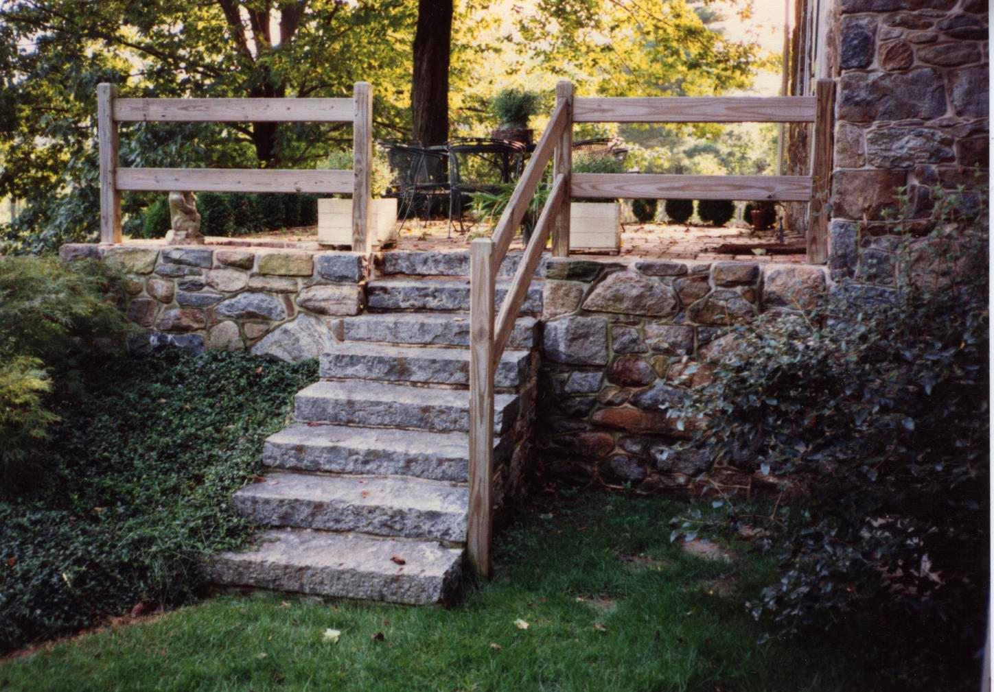 A Stone Wall And With Stone Steps Leading Up To A Stone Patio. A Wood