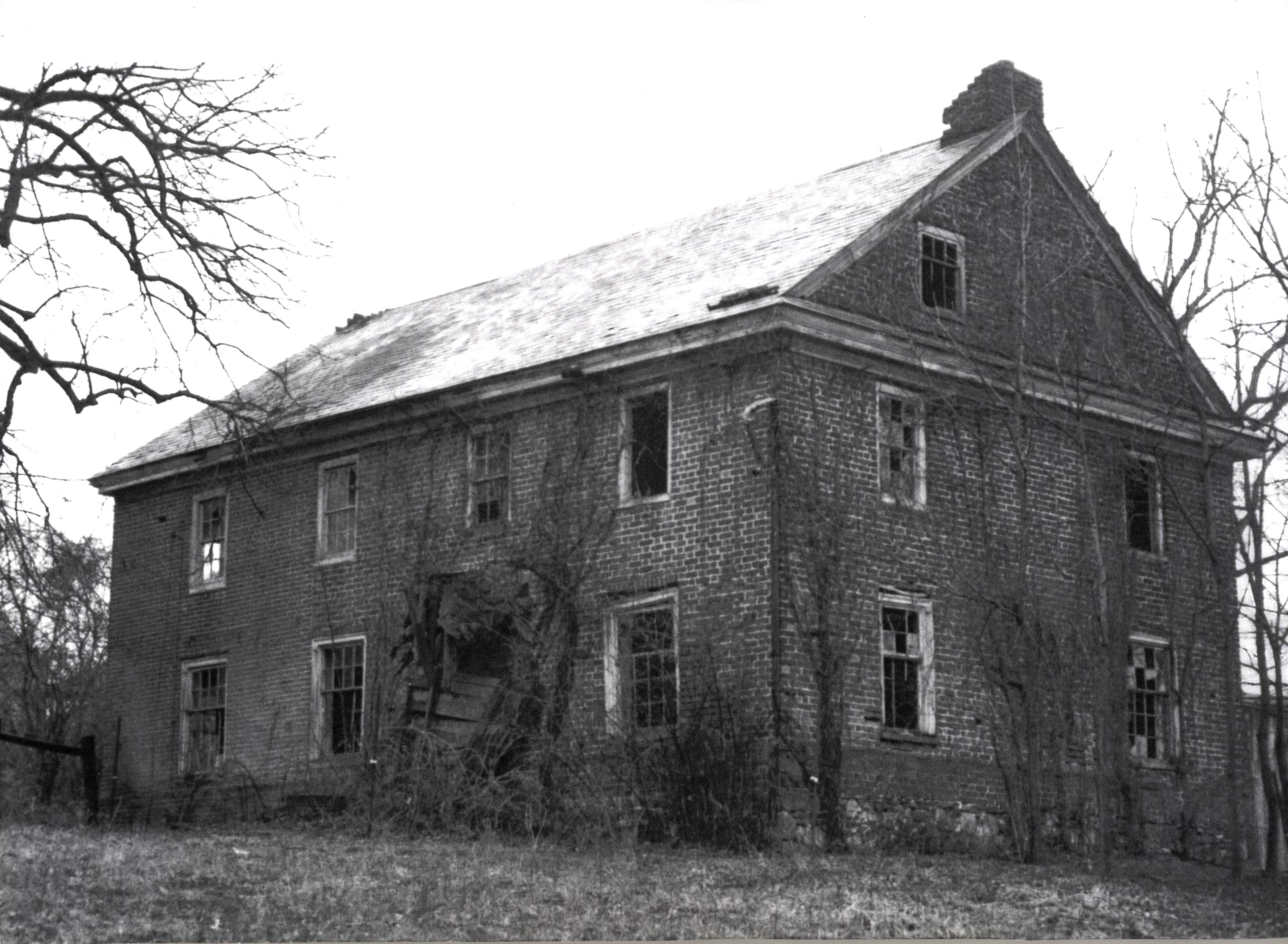 An old home with broken windows, a collapsed entryway, and visible damage to the roof, walls and chimney.