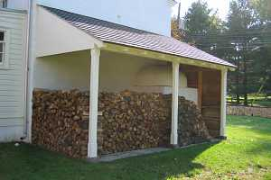 Firewood stacked beside the outside of a beehive bake oven