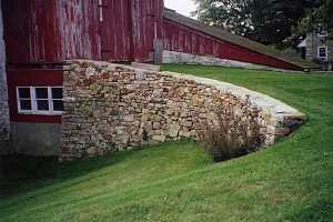 a curved natural stone wall that leads a grass path to an old red barn