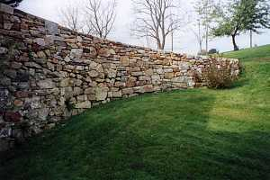 a curved natural stone wall on a grassy hill