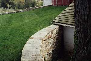 a curved natural stone wall on a grassy hill leading to an old barn