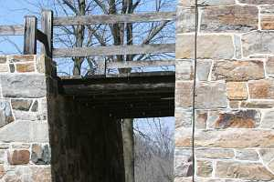 a bridge between a barn and a natural stone wall