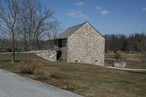 a historic stone barn and a rebuilt natural stone bridge