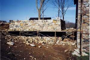 scaffolding around a natural stone wall. the ground is littered with stone pieces