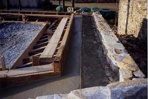 the top of a natural stone wall and the frame for a barn bridge that is going on top.