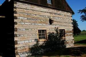 new wall of a log cabin with custom cut stones