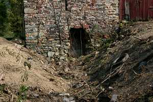 eroded land around a damaged wall of an old barn