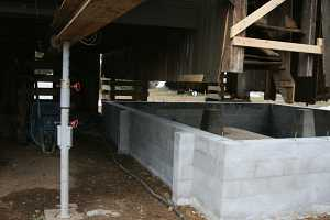 barn suspended above new concrete cinderblock foundation