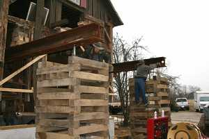 barn being raised by workers on top of steel beams