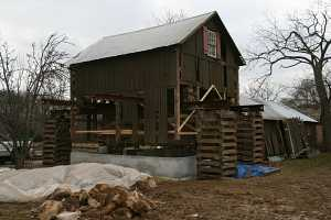 barn suspended above new concrete foundation