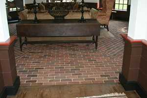 a sitting area with a red brick floor