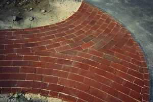 a circle parttern brick patio leading to a driveway
