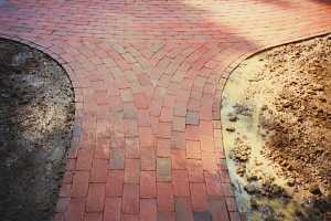 a rounded brick walkway converging on a brick sidewalk