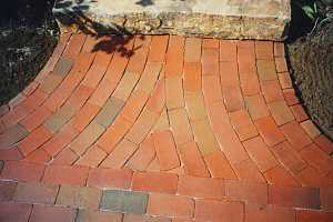 a rounded brick pattern leading to a stone step