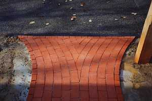 a rounded brick pattern leading to an asphalt driveway
