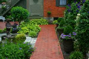 a brick patio area that includes a pond and many planters, shrubs and other outdoor features