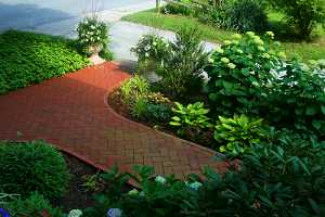 a brick walkway running parallel to a stone driveway and between two gardens full of shrubs