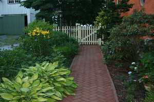 a brick walkway between two gardens leading to a white picket fence