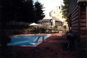 a brick patio around a pool area. a grill is in the foreground with patio chairs and a table in the background