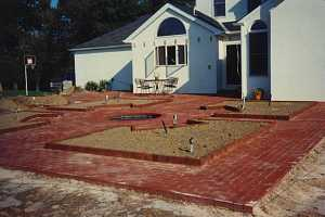 a newly installed decorative brick patio with 4 visible planting areas included