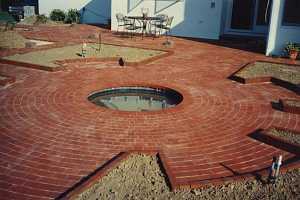 a newly installed brick patio with a round pond in the middle