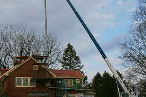 A chimney duct suspended by a crane in preparation for installation
