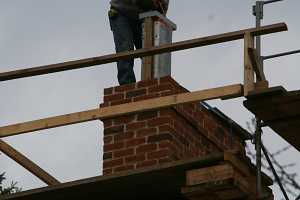 A chimney duct being installed via crane