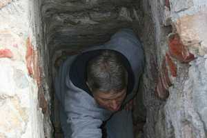 A man repairing an old chimney flue