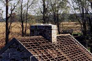 A stone chimney and roof without shingles