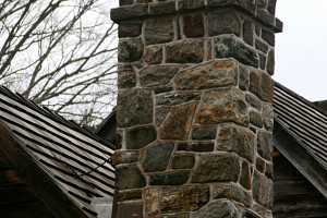 A decorative stone chimney with arch