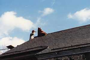 A man providing chimney services to a broken brick chimney