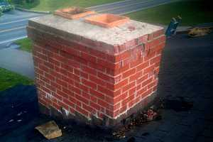 A cracked brick chimney beginning to break down