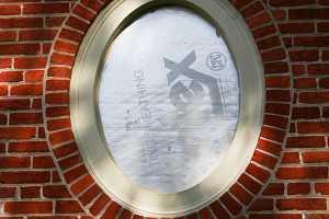 a restored round window on a brick home