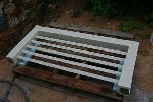 a wooden window grate sitting on a wooden skid