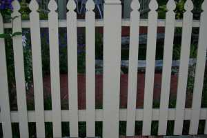 a brick walkway around a white picket fence with a gazebo in the background