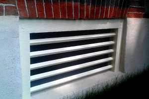 a painted wooden window grate in a concrete base of a brick home