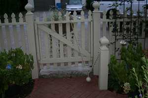 a white picket fence with a white concrete block under the door surrounded by a brick walkway