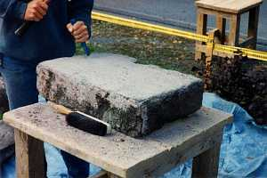 A large stone being formed by a chisel and hammer