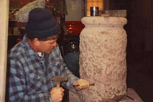 A stonemason beginning to form an outdoor sundial pillar