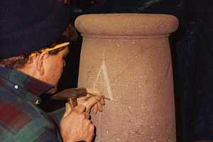 A stonemason carving letters into what will be a sundial pillar