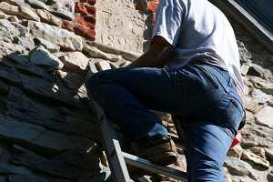 Stonemason examining an old date stone in need of refurbishment