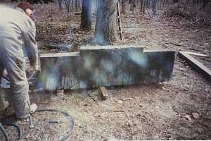 cement base standing on three wood planks in the woods