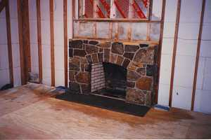 a natural stone fireplace with a wall frame and no drywall around it