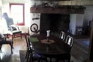 a historic kitchen with a brick fireplace in the background