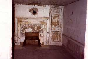 an old fireplace area with chipping white paint and wall pieces - before